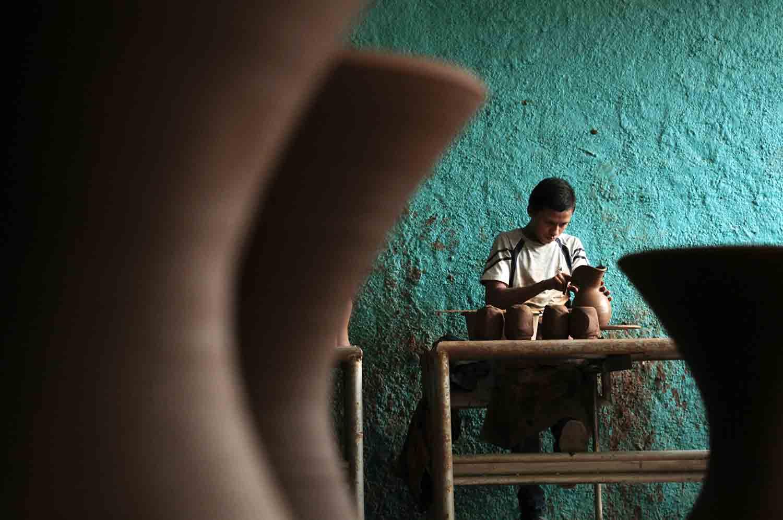 34-Un joven alfarero trabaja torneando diferentes jarrones en un cetro artesanal. Ilobasco 2015.