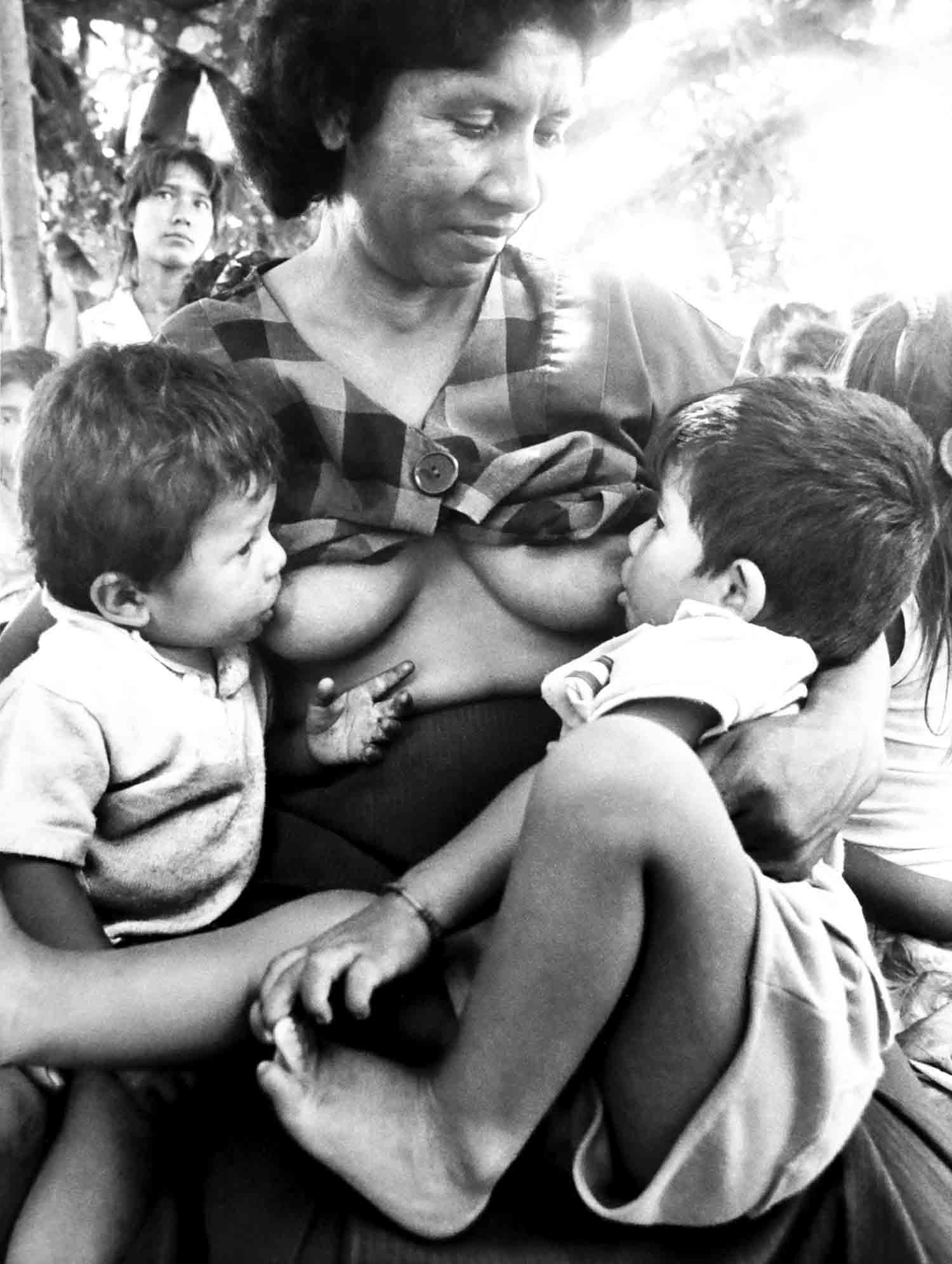 37-Una madre salvadoreña da de amamantar a sus hijos en el caserío San Antonio. Suchitoto septiembre de 1988 Foto Luis Galdámez