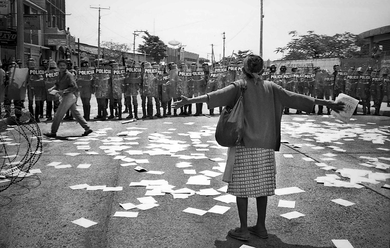7-Una mujer protesta frente a miembros de la Policía. Manifestantes fueron dispersados con disparos.San Salvador julio 1998.