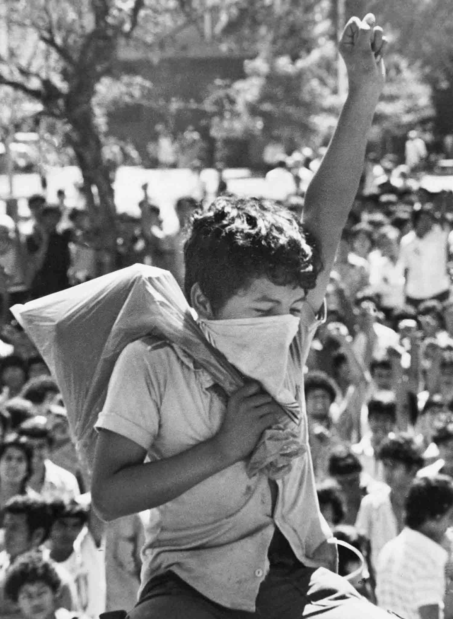 Un niño con su mano en alto participa de una protesta frente a catedral. San Salvador Junio 1979.