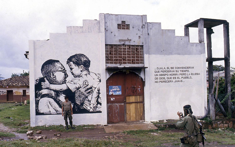 Un soldado posa para una fotografía durante un operativo militar frente a un mural de Monseñor Óscar Arnulfo Romero. Morazán, agosto de 1987.