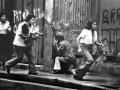 2-Una familia se desplaza frente a una persona armada durante los disturbios del sepelio de Monseñor Romero en San Salvador.30 de marzo de 1980